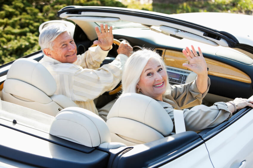 Senior couple (60s, 70s) having fun driving away in convertible.  Focus on woman.